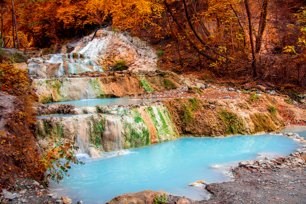 light blue hot spring with red rocks surrounding day trips from Florence