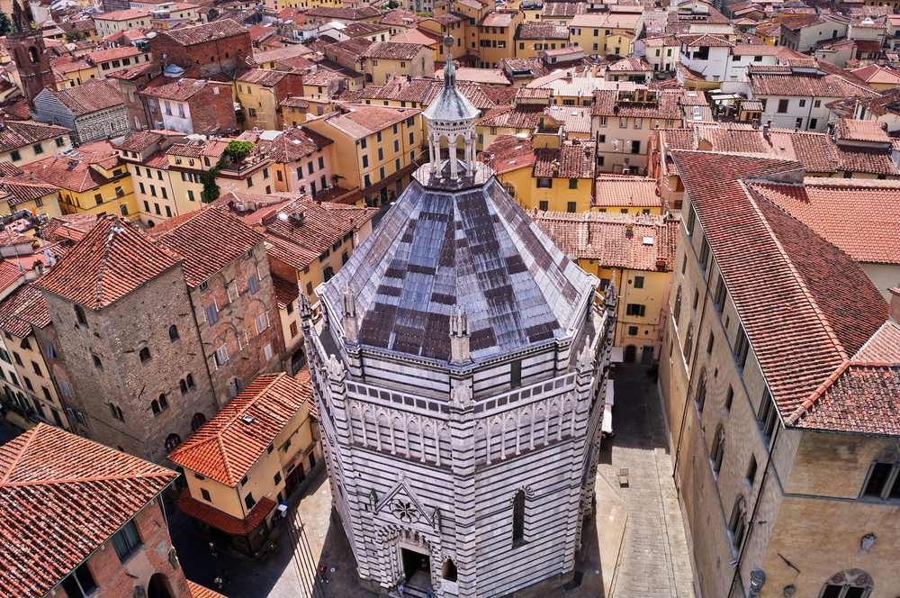 black and white baptistery in Pistoia surrounded by reddish buildings