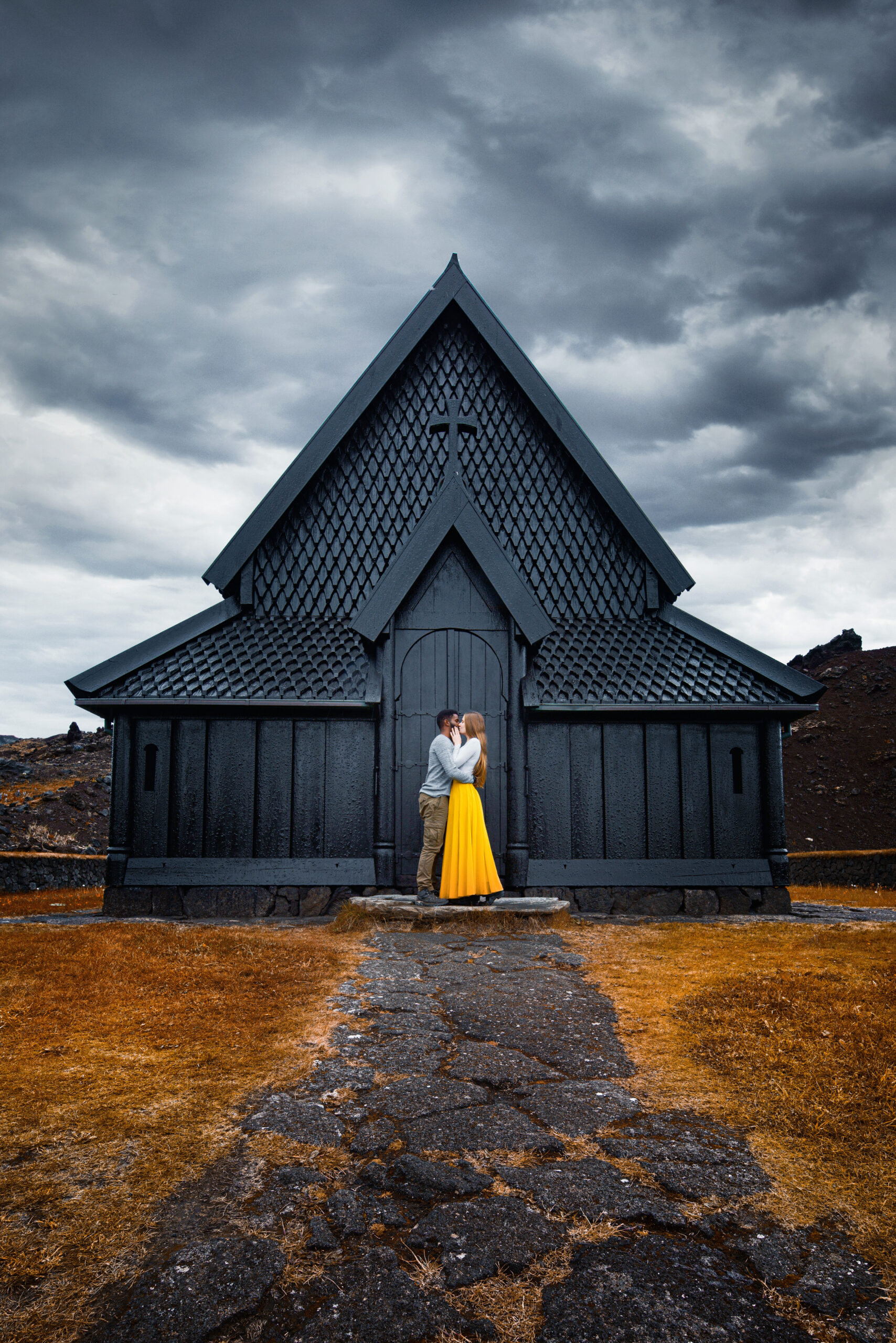 Couple standing in front of black church, one of the hidden gems in Iceland