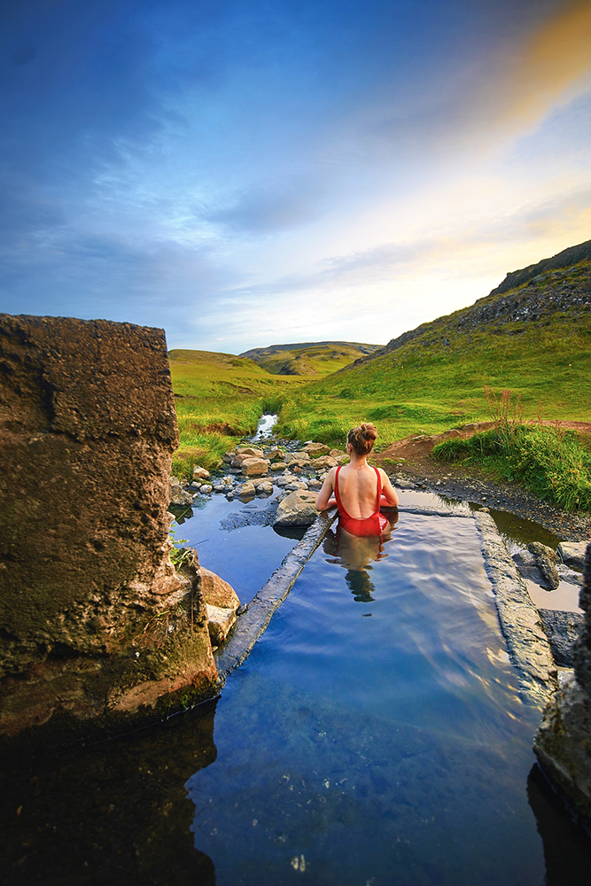 Woman in red bathing suit laying in secret hot spring in Iceland