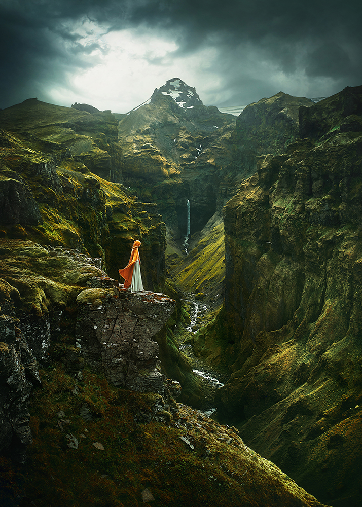 Woman in yellow cape standing in a cliff at Mulagljufur Canyon, one of the hidden gems in Iceland