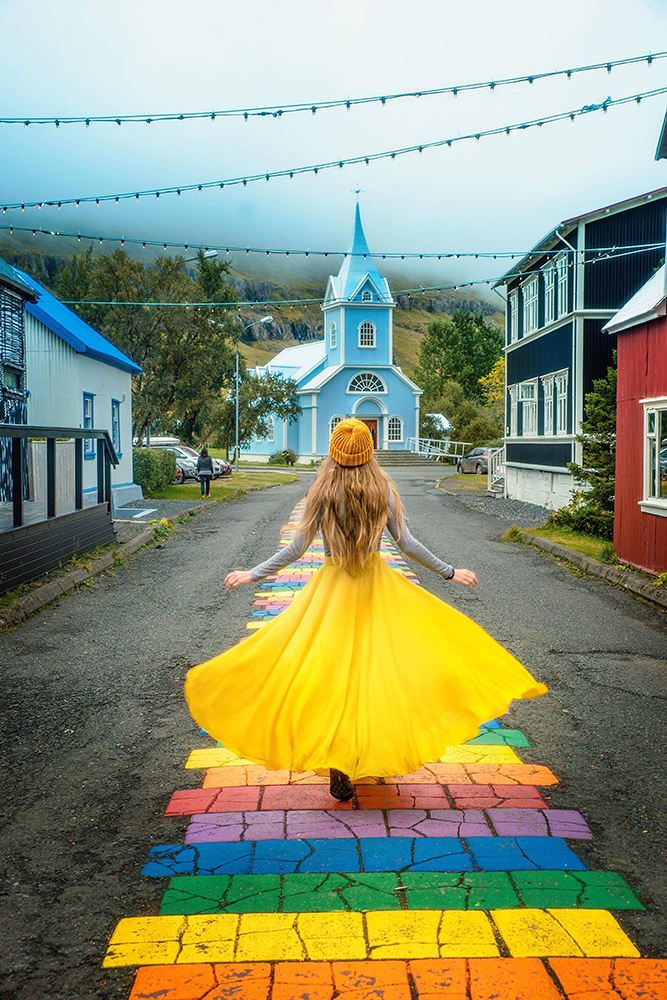 Woman in yellow dress walking in Seydisfjordur towards a blue church, one of the hidden gems in Iceland