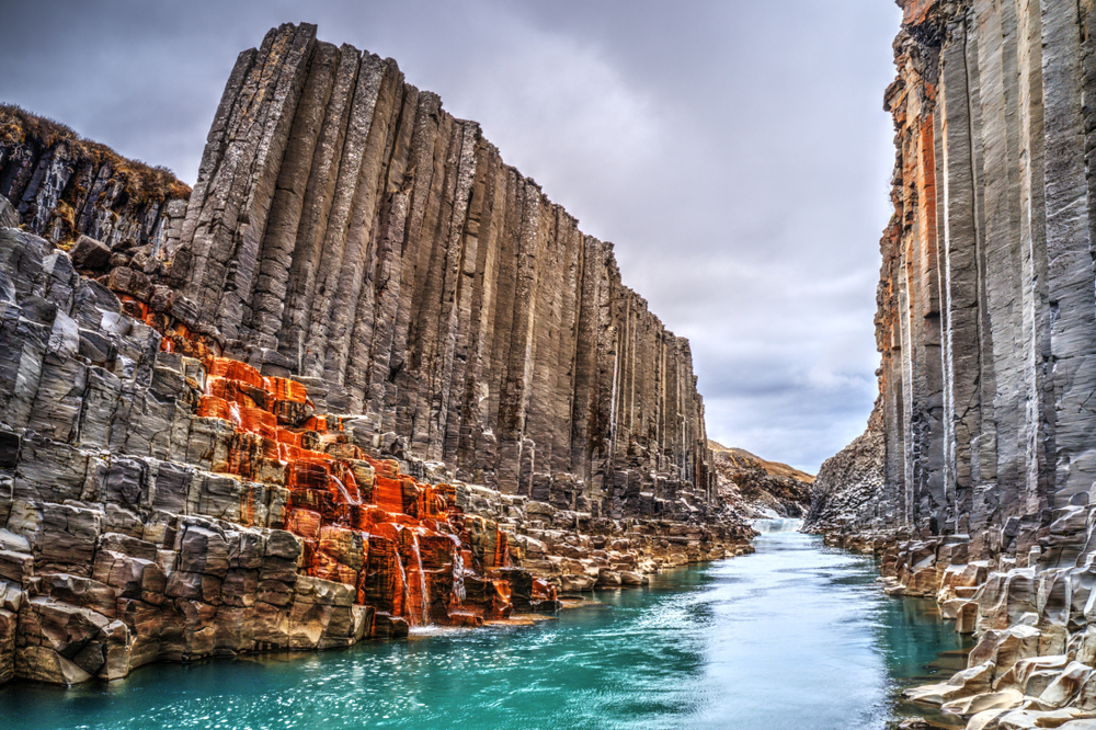 River flowing through the black basalt columns of Studlagil Canyon, one of the hidden gems in Iceland