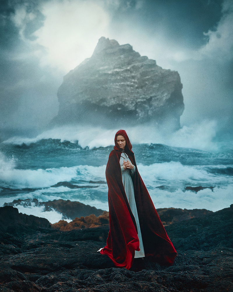 Woman in long, red cape standing in front of ocean and large rock in Iceland