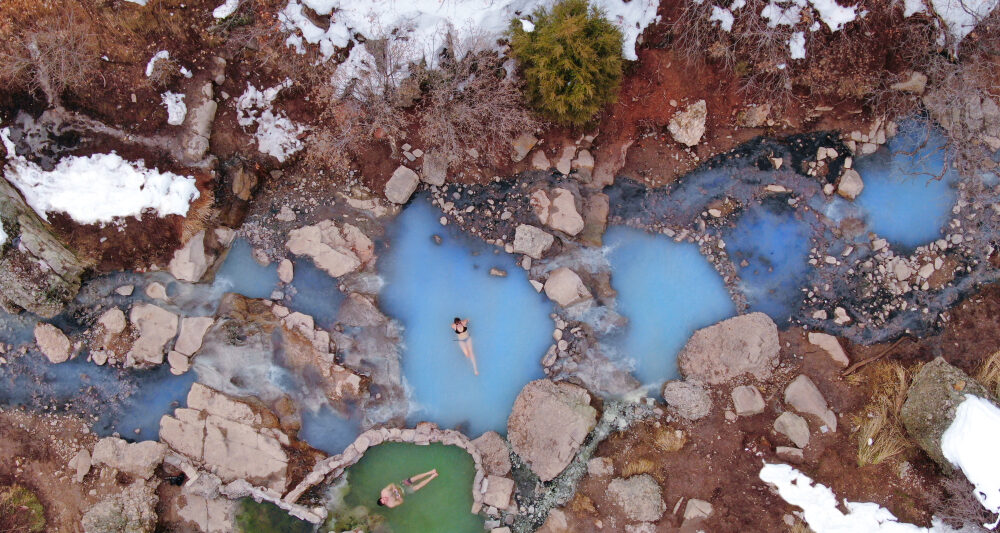 Diamond Fork Hot Springs in Utah. A sky view of two bathers in a milky blue hot springs surrounded by snow covered rocks.