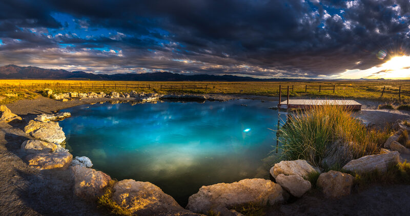 Meadow Hot Springs. A crystal clear pool with a small dock rests on a grassy cattle range at dusk.