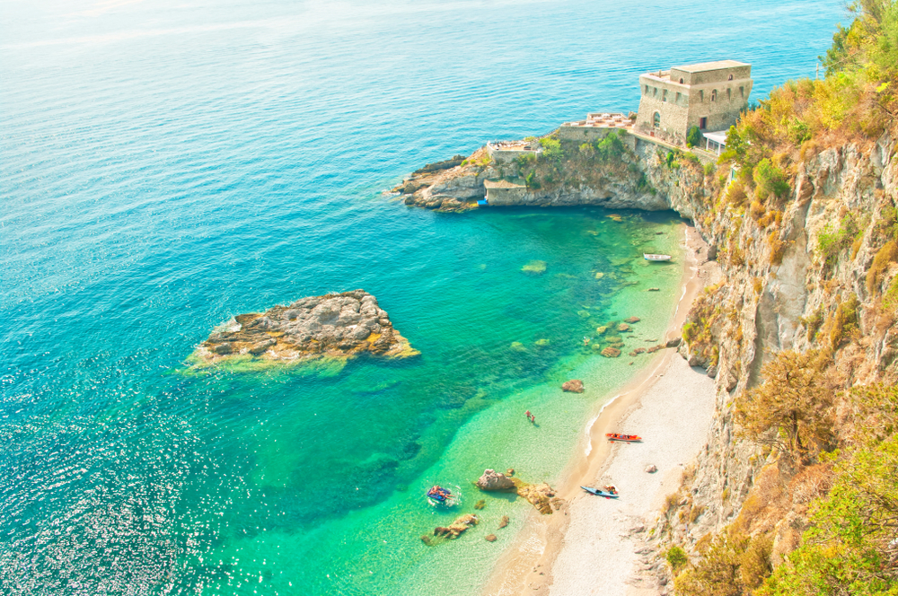 Aerial view of Erchie, one of the prettiest beach towns in Italy with gorgeous green water.