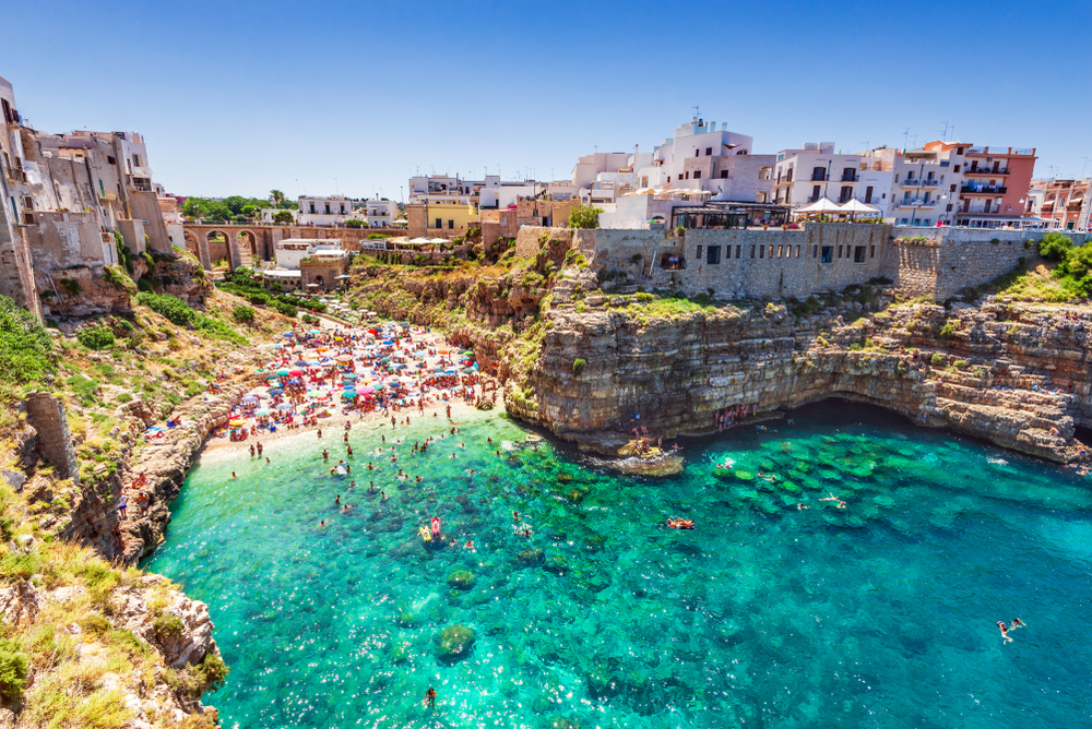 Vibrant turquoise waters leading to a beautiful beach and one of the prettiest beach towns in Italy, Polignano a Mare.