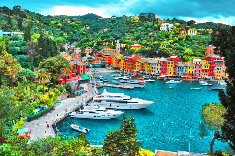View of Portofino's bright, colorful town and harbor filled with luxurious yachts.