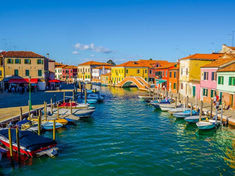 A view of Murano from a canal filled with colorful boats.