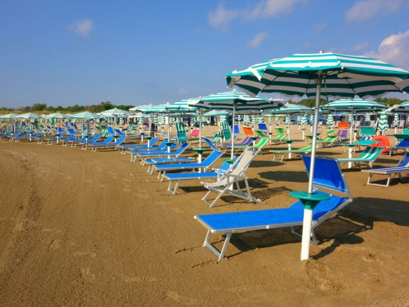 Alberoni beach on a sunny day with blue lounge chairs and teal umbrellas lined up in a row.