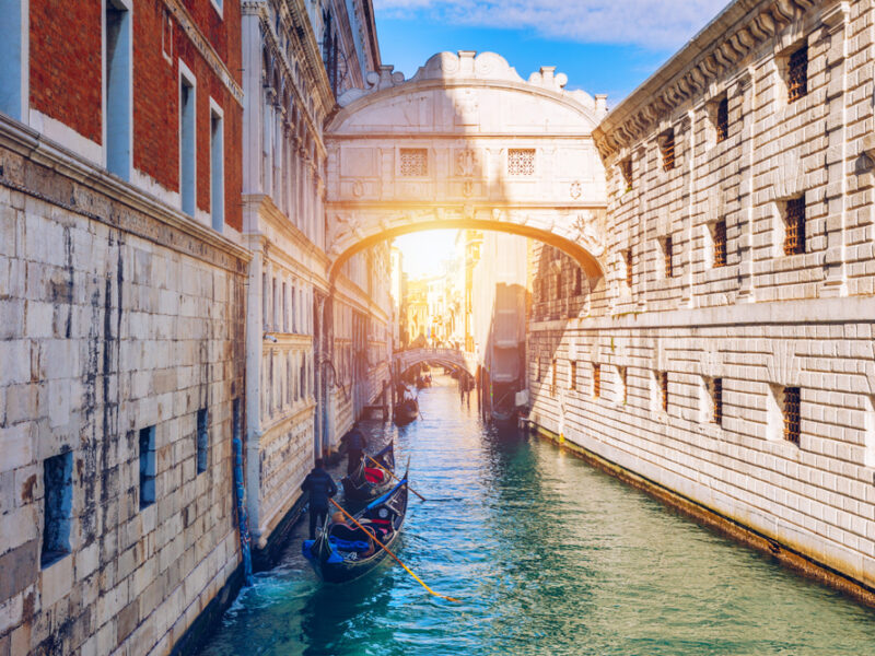 A gondola floats on a canal beneath The Bridge of Sighs in Venice Italy.