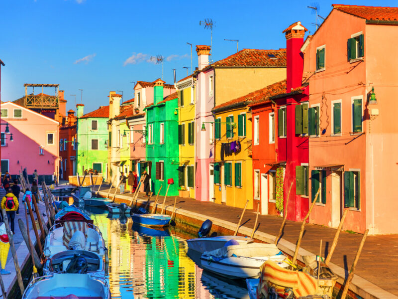 Colorful boats and buildings line a small canal in Burano Italy.