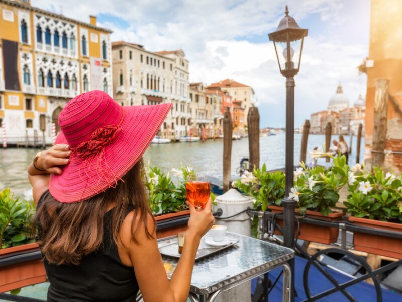 A classy woman in a red sun hat sips wine at a Venetian cafe overlooking the canal.