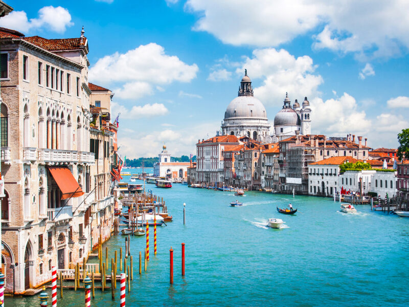 A view of The Grand Canal in Venice, Italy with its teal waters and busy boat activity.