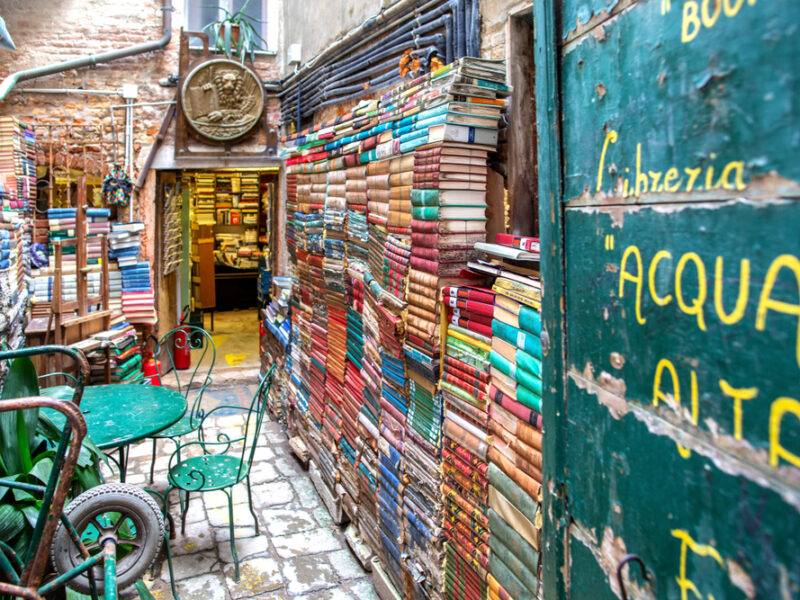 The charming bookstore, Libreria Alta, with wall made out of stacked books and a small cafe table and chairs.