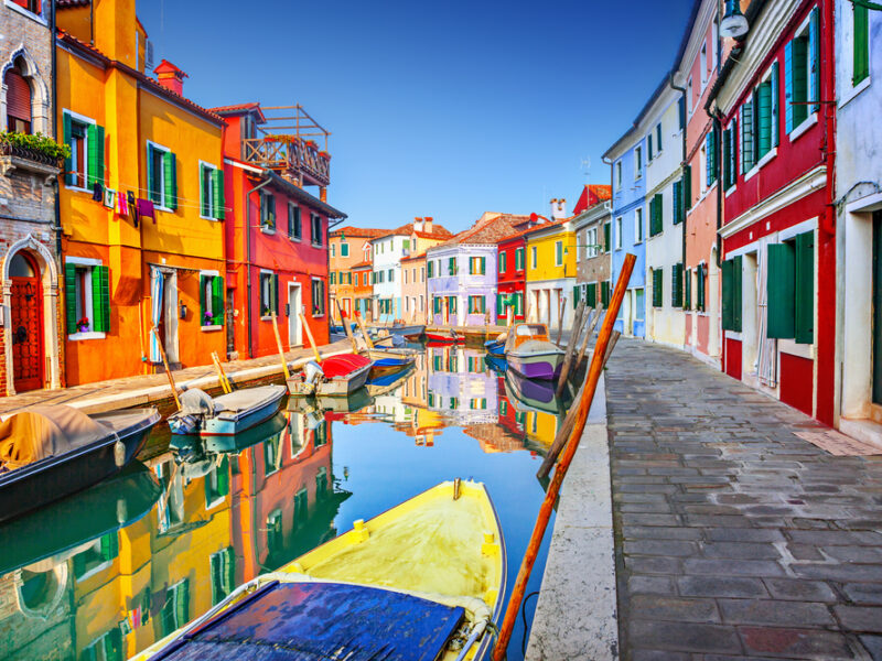 A scene of vivid colors, a line of bright buildings extends up along a peaceful canal.