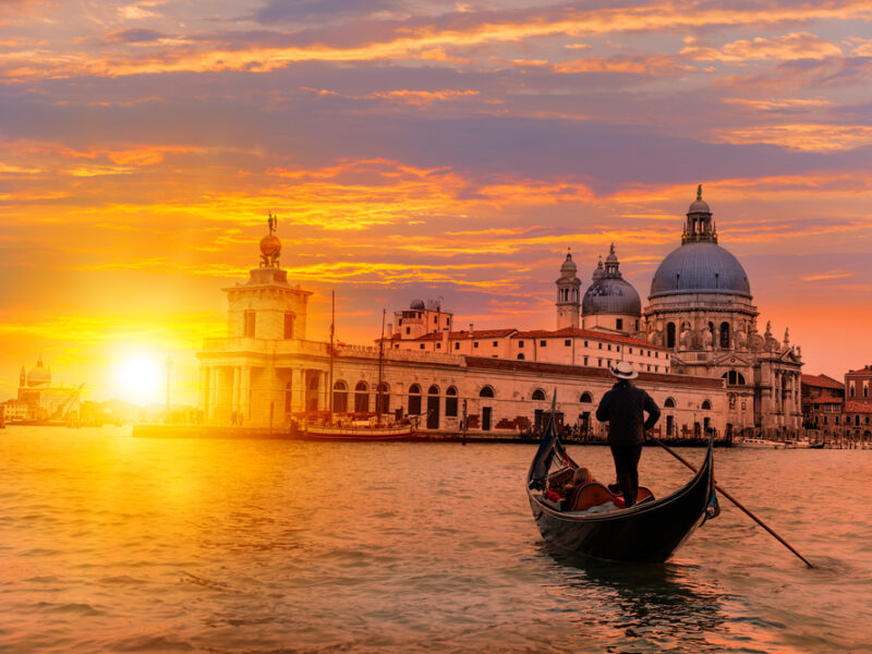 A gondola floats in The Grand Canal at sunset in Venice, Italy.