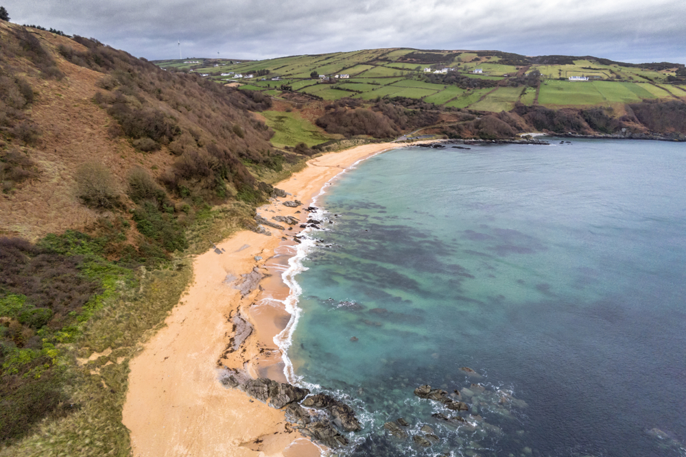 Arial view of Kinnagoe Bay's beautiful turquoise water against the shore.