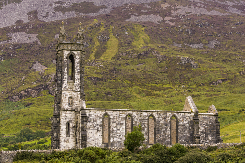 The best things to do in Donegal includes seeing Dunlewey Church ruins in Poisoned Glen beneath a mountain.