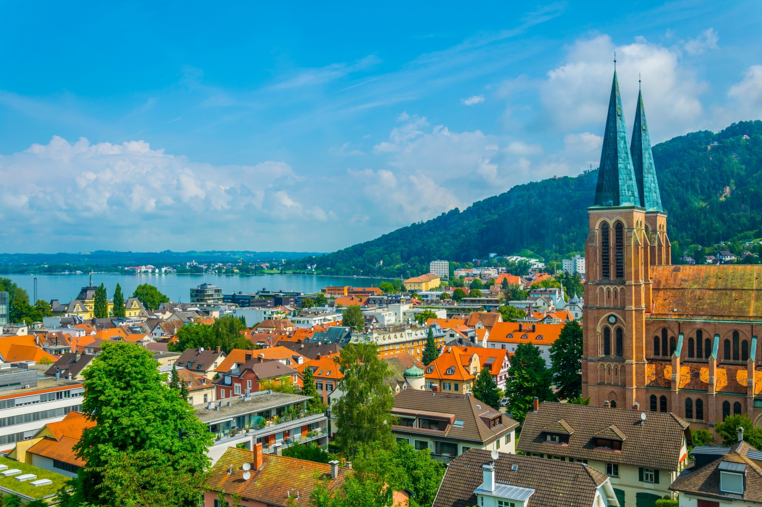 Photo of the small Austrian town Bregenz. The very unique double steeple church is shown on the right with many buildings and homes scattered on the left. Light blue water is far in the background with a green mountain on the right.