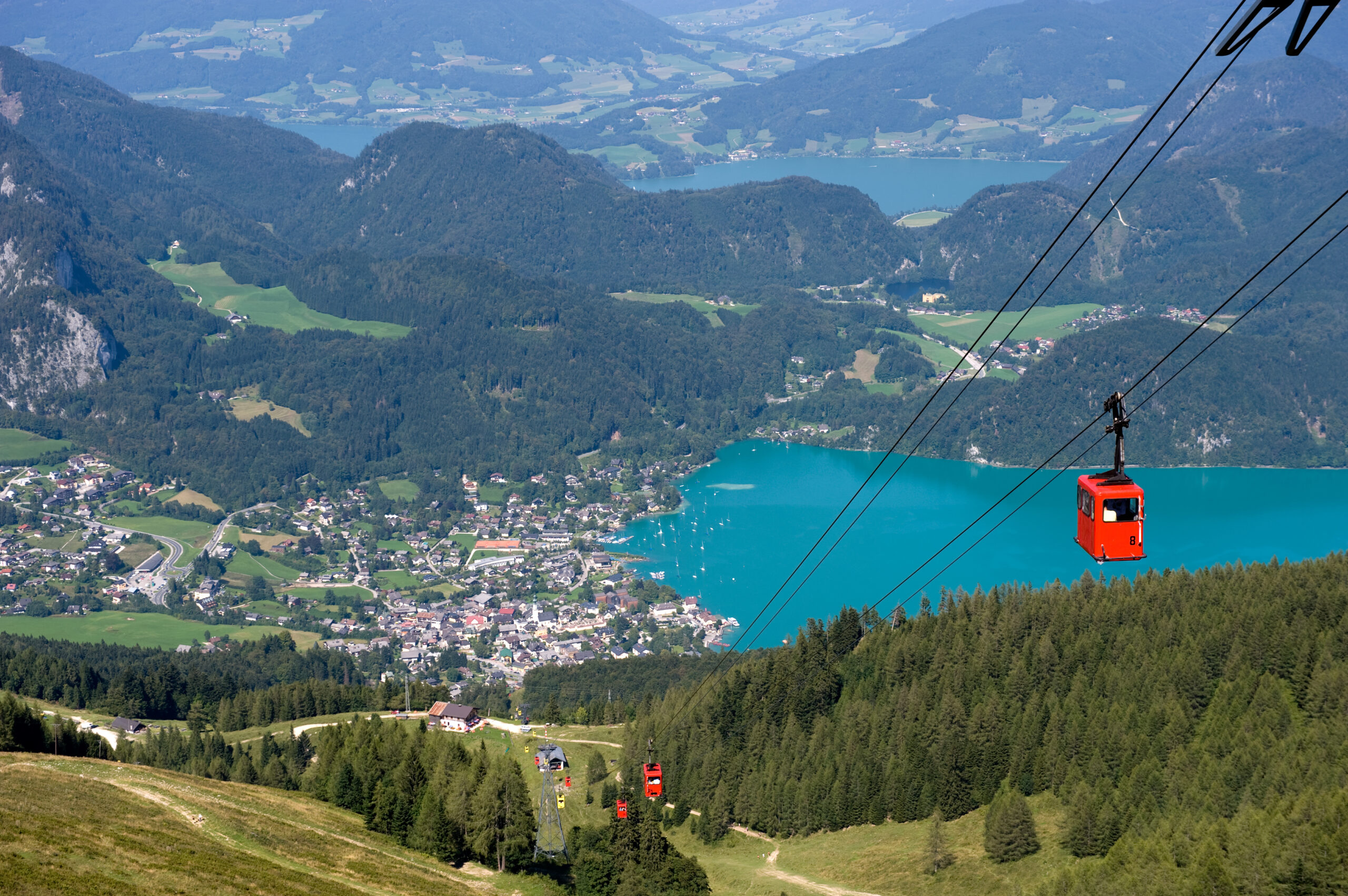 Photo of bright red cable car ascending an Alpine mountain. Small Austrian town with mountains and a brilliant blue lake are featured in the background.