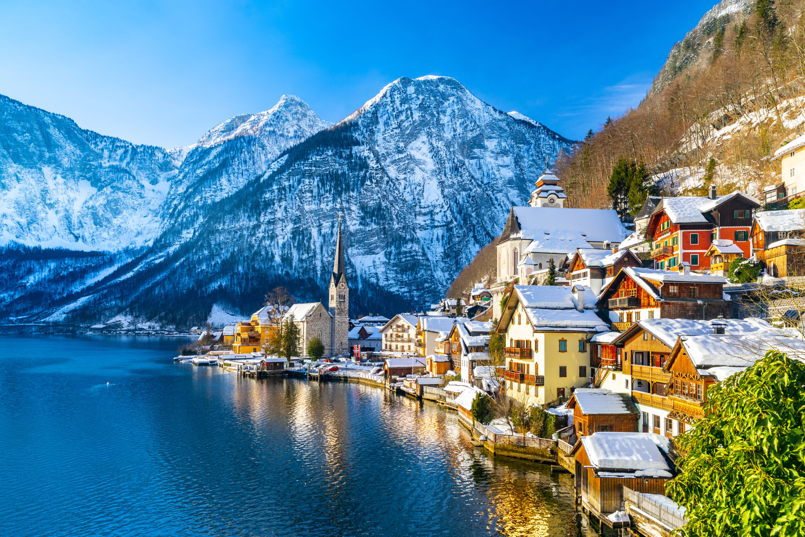 Photo of Hallstat, a small town in Austria, during winter. Colorful snow covered cottages are situated alongside a beautiful lake with a massive snowy mountain in the background.