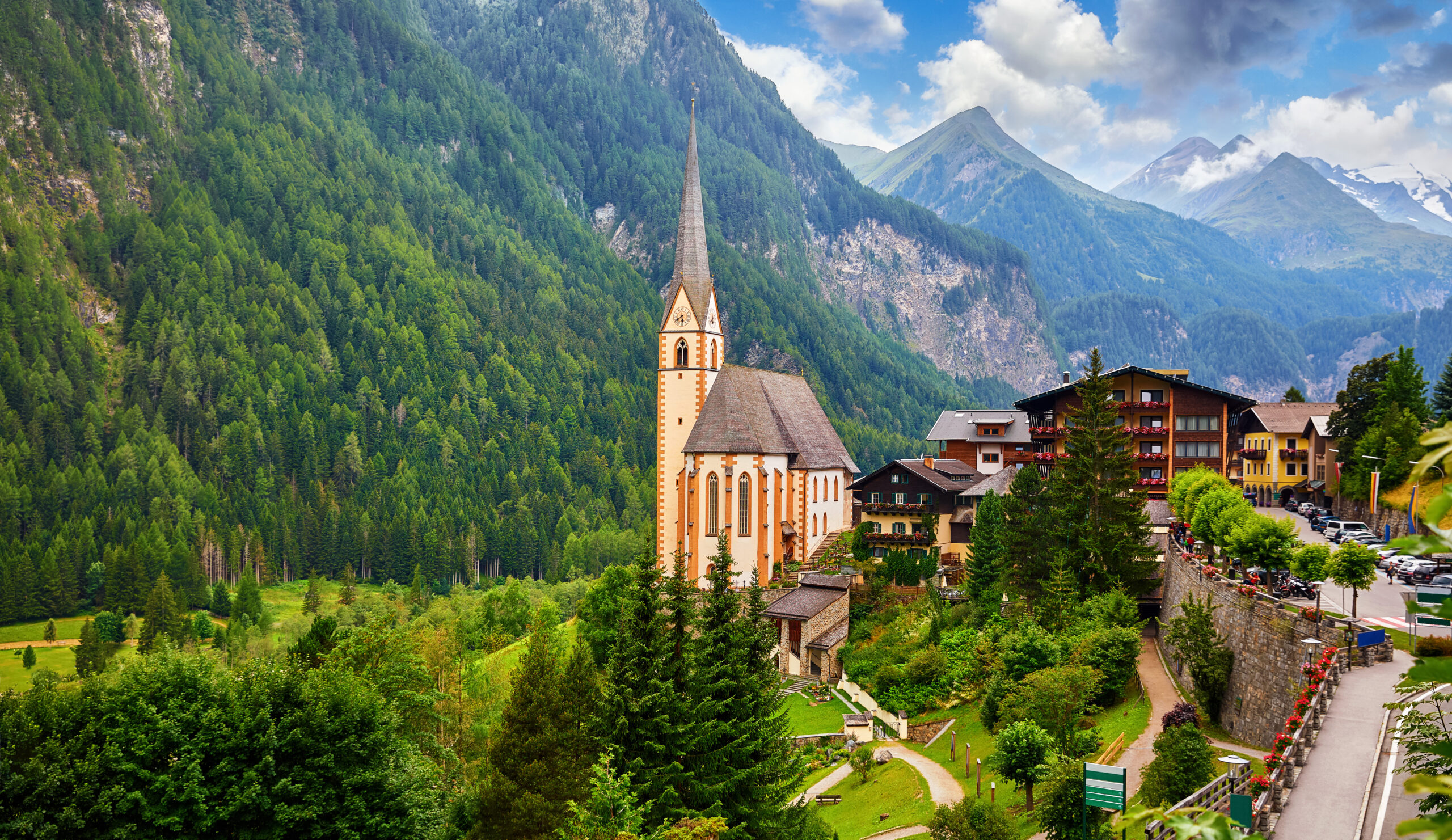 Photo of the small Austrian town of Heliligenblut featuring an ariel view of St. Vincent's Church with Grossglockner Mountain in the background.