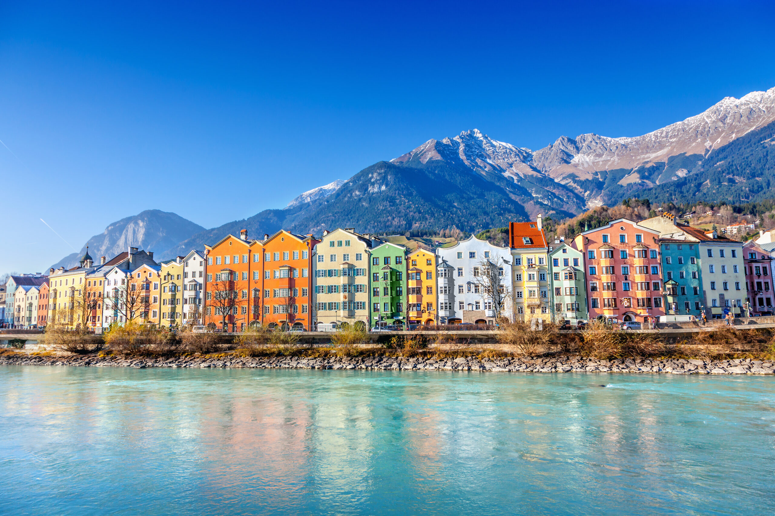 Photo of the small Austrian town of Innsbruck. An icy blue lake is seen in the foreground. Multi-level and multi-colored residences are featured in the middle with a slightly snowy mountain in the background.