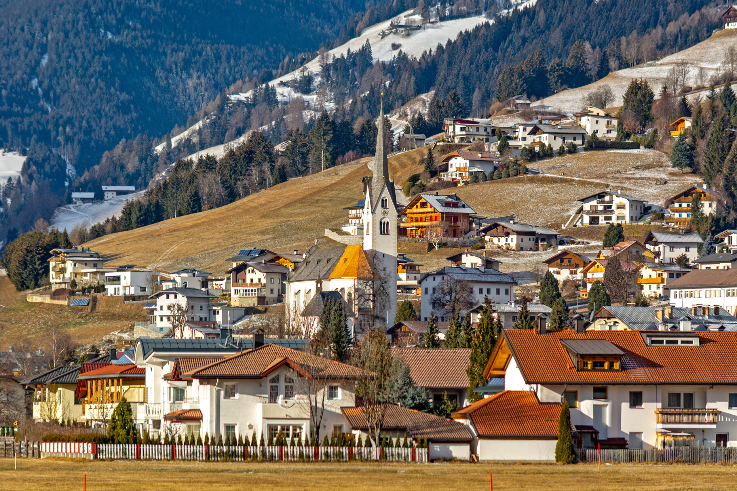 Photo of the small Austrian town Lienz. Homes are scattered at the base of a mountain. A church is seen right in the center of the town. Snowy mountains are in the far background as the elevation increases.