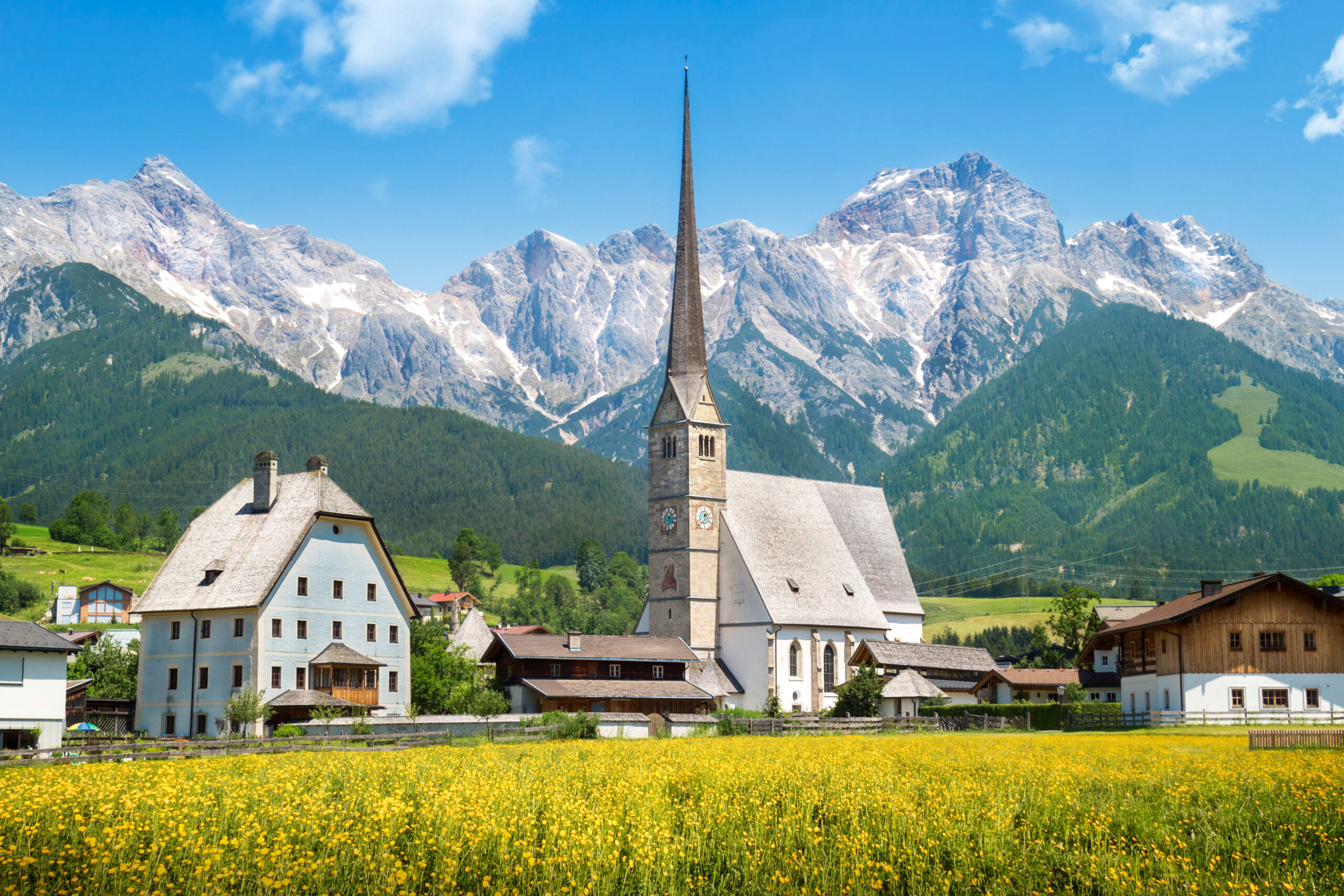 Photo of Maria Alm, a small town in Austria. Lime green grasses are seen the the foreground. A church is in the middle with some smaller buildings on either side. There is a beautiful contrast of lush green and snowy mountains in the background.