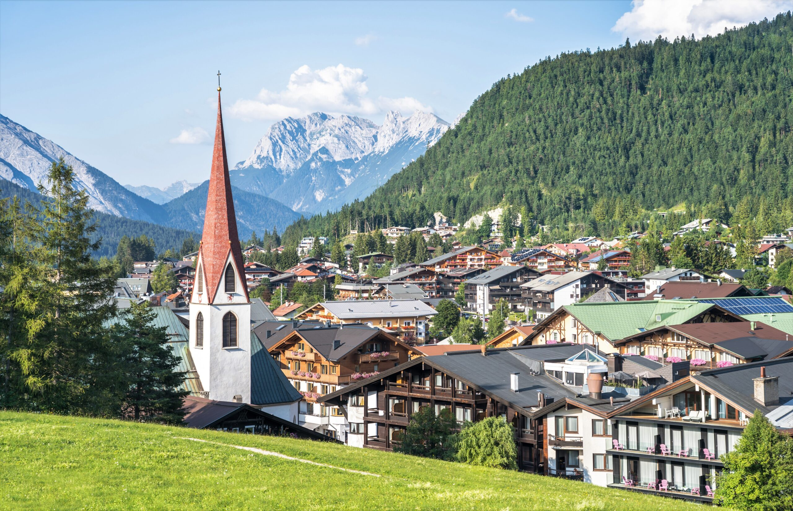 Photo featuring the Alpine landscape of Seefeld in Tyrol. Several small ski lodges are seen at the base of a green mountain. A church with a brick steeple is on the left side. Snow capped mountains are far in the background of this small town in Austria.