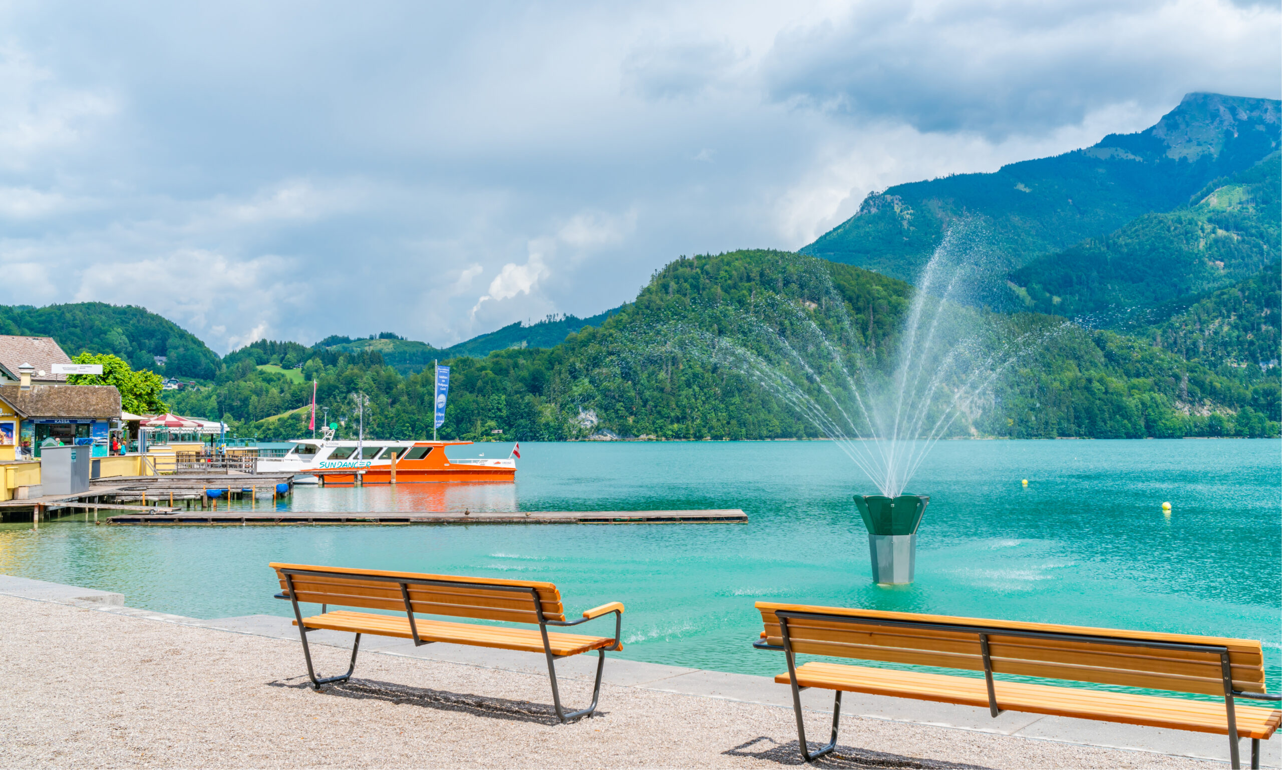 Photo of the stunning blue waters of the Wolfgangsee in St. Gilgen. A small shop with a dock and boat are featured on the left. Two wooden benches are in the foreground facing the Wolfgangsee water that has a pretty fountain in the middle. Lush green mountains are in the background.