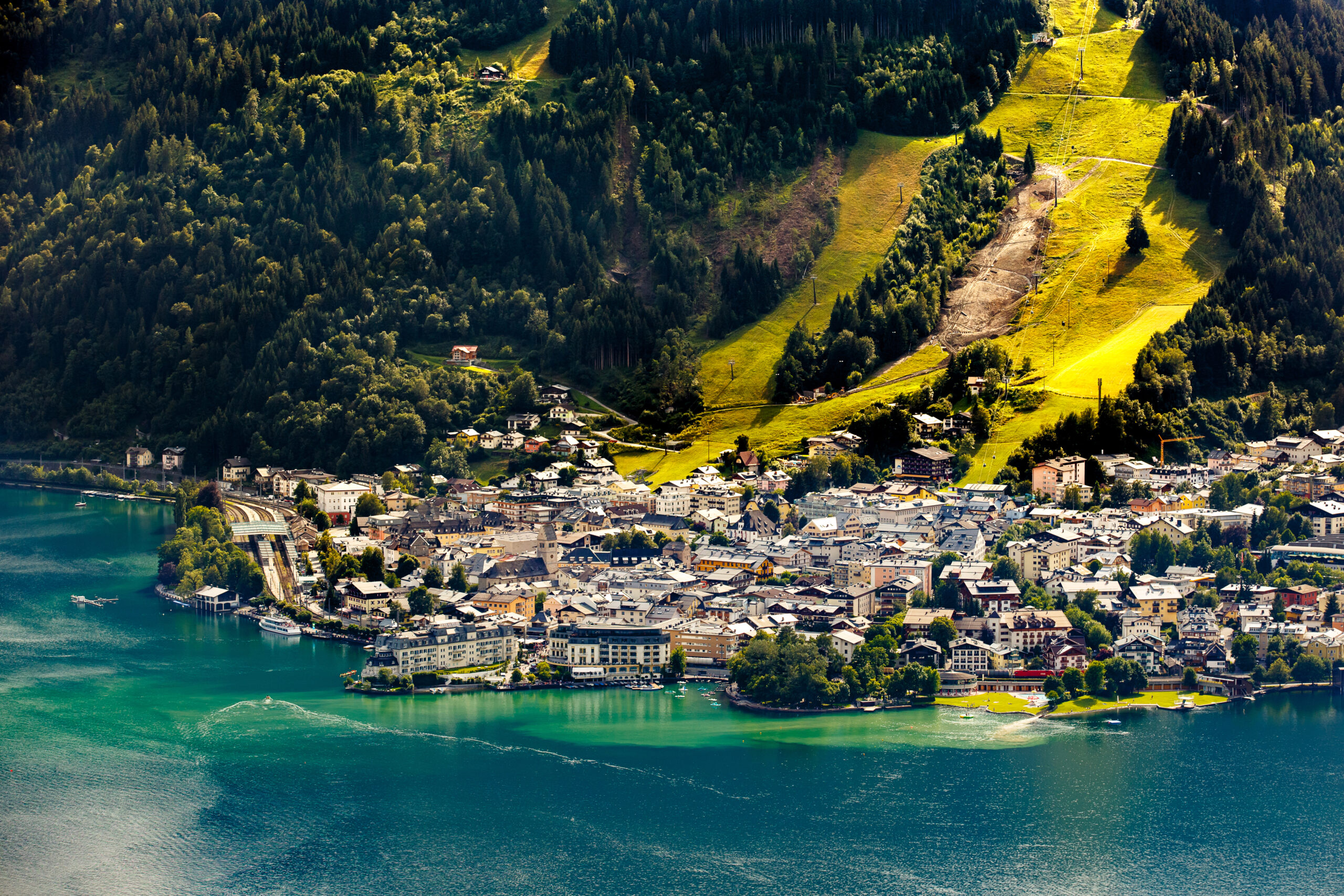 Photo featuring an amazing aerial view of Zell am See. Blue-green water is in the foreground. There are many waterfront resorts seen with just as many homes and buildings behind them. Light green grass is shown on large ski runs going up the mountain side. Dark green trees are on either side.