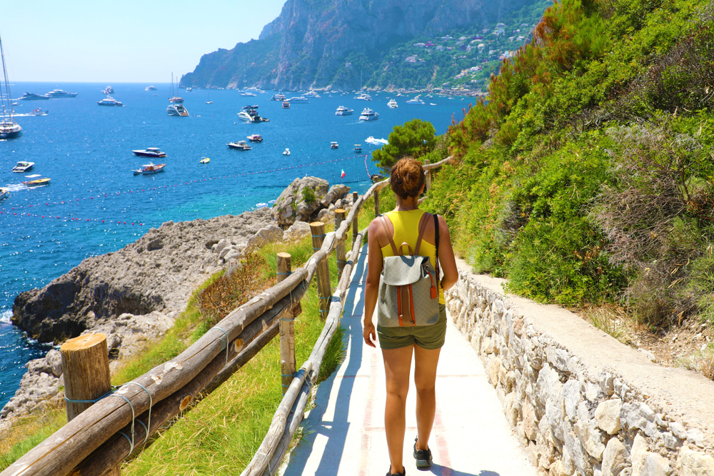 Photo of girl hiking, a great example of a free activity to lower your trip to Italy cost.