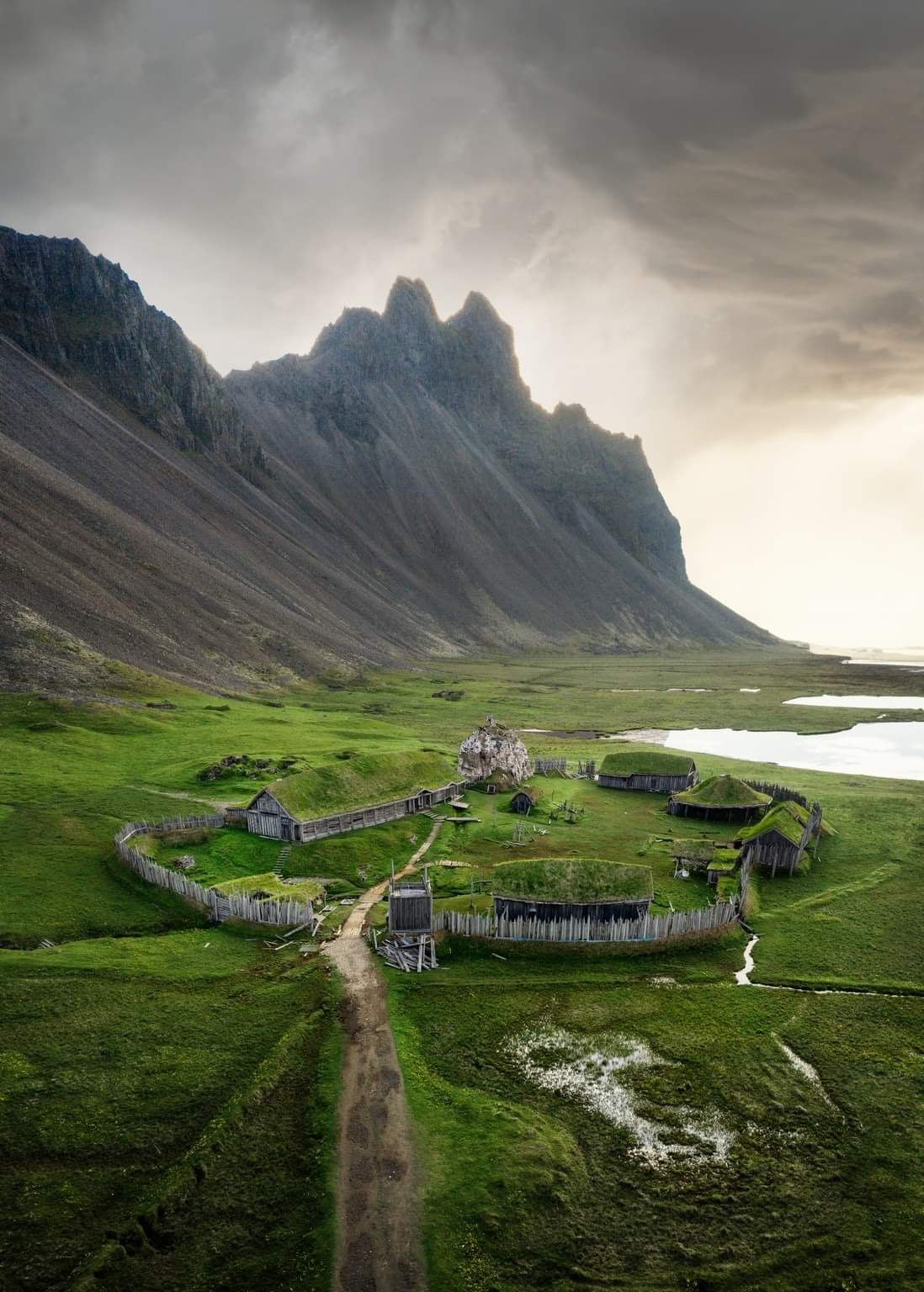Aerial shot of small fake Viking village with mountains in background in Iceland