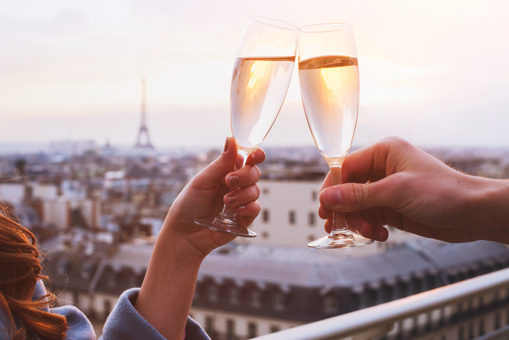 photos of two people clinking wine glasses with the Eiffel tower in the background