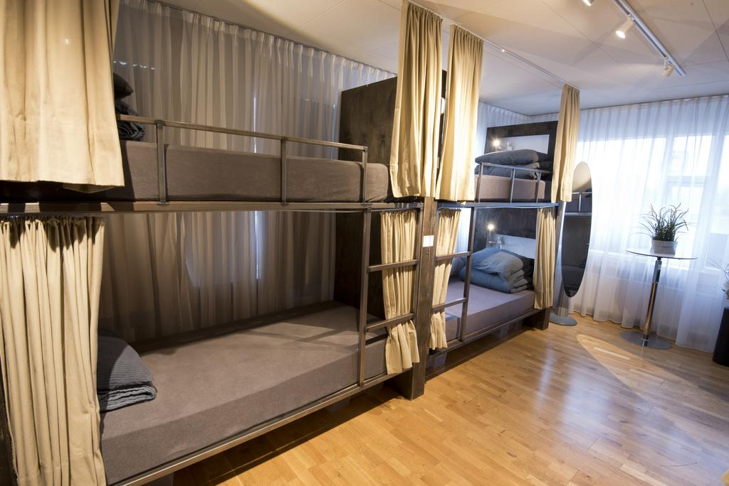 Photo of dorm style accomodations at B14 Hostel located in Reykjavik Iceland. Bunk style beds are seen with ivory curtains.