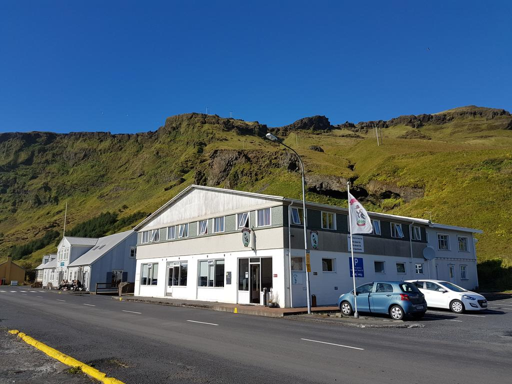 Photo of Puffin Hotel located in Vik Iceland. Small gray and white building is seen with a small mountain in the background.