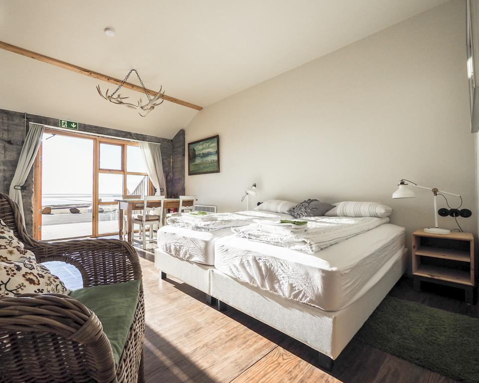 Photo of a guest room at The Garage Apartments located in Vik Iceland. A crisp and light decor is seen in this well appointed room. Bed linens are neatly folded and placed at the foot of the beds. A wicker chair is seen in the foreground.