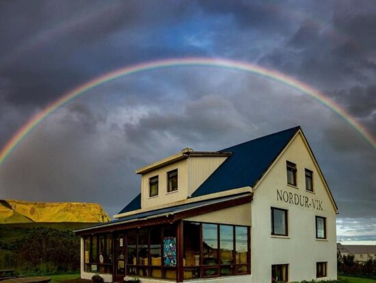 Photo of Vik Hostel in Vik Iceland. A pale yellow farmhouse is seen with a dark blue roof. Picnic tables are located outside of the building. A rainbow is right above with stormy clouds.