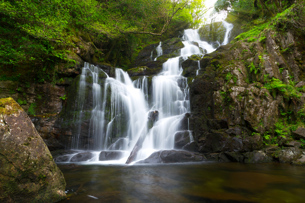 White water cascading down the mountain at Torc Waterfall, a beautiful place in Ireland to visit.