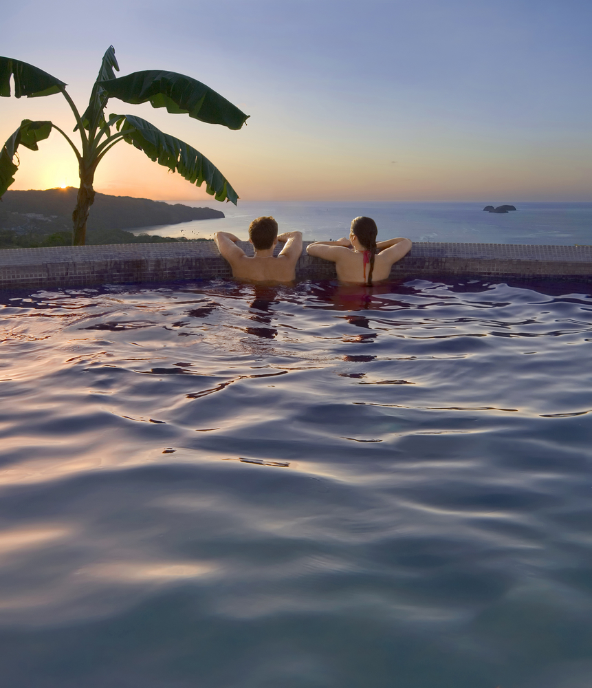 couple enjoying the pool at their resort on their costa rica honeymoon