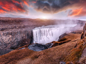 photo of the iconic Dettifoss waterfall, one of the most powerful waterfalls in the world. There is a dramatic sunset sky in the background