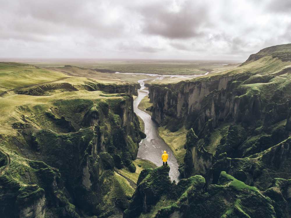 Fjadrargljufur Canyon with person standing in yellow raincoat