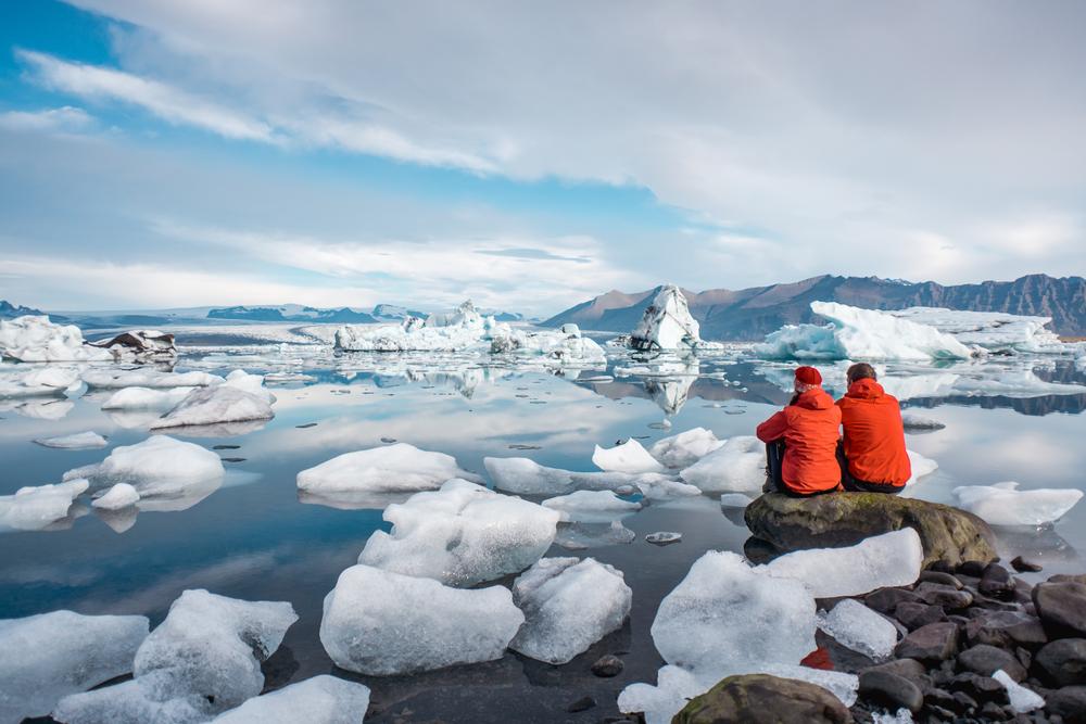 Two tourists sitting and looking at jokulsarlon glacier lagoon