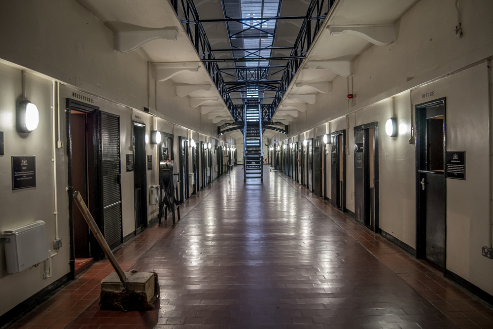 Photo of the inside of Crumlin Road Gaol, one of the most popular things to do in northern ireland. The photo shows a long white hallway with jail cells on both sides.