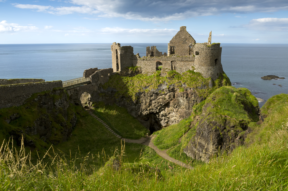 Photo of the ruins of Dunluce Castle. It's situated on a cliff with the sea in the background, one of the many things to do in Northern Ireland.