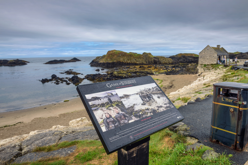 A Game of Thrones Tour is one of the things to do in Northern Ireland for fans. This photo shows a beach in the background with a plaque in the foreground with information about the filming location