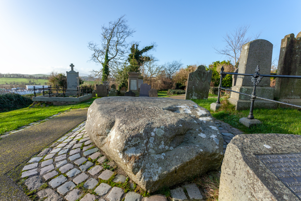 Visting St. Patrick's Grave is one of the things to do in Northern Ireland that tourists take part in. The grave is situated in a churchyard with a massive stone covering it for protection.
